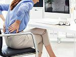 Woman Suffering With Back Pain At Work